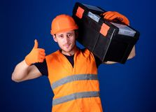 Man in helmet, hard hat holds toolbox and shows thumb up gesture, blue background. Repair consultation concept. Worker. Repairer, repairman, builder on stock photography