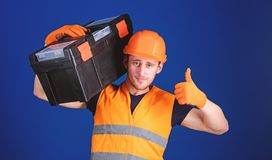 Man in helmet, hard hat holds toolbox and shows thumb up gesture, blue background. Worker, repairer, repairman, builder. On confident face carries toolbox on royalty free stock photo