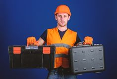 Man in helmet, hard hat holds toolbox and suitcase with tools, blue background. Toolbox and equipment concept. Worker. Repairer, repairman, builder on stock photography