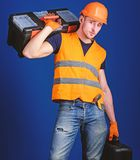 Man in helmet, hard hat holds toolbox and suitcase with tools, blue background. Worker, repairer, repairman, builder on. Calm face carries toolbox on shoulder stock photo
