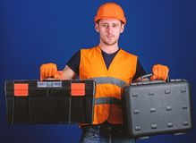 Man in helmet, hard hat holds toolbox and suitcase with tools, blue background. Worker, repairer, repairman, builder on. Thoughtful face choosing equipment for royalty free stock images