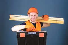 Man in helmet, hard hat holds toolbox and wooden beams, grey background. Carpenter, labourer, builder, woodworker on. Happy face carries wooden beams on stock photography