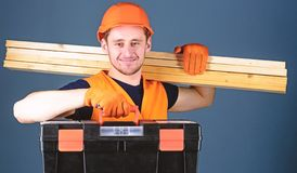 Man in helmet, hard hat holds toolbox and wooden beams, grey background. Carpenter, labourer, builder, woodworker on. Smiling face carries wooden beams on stock photo