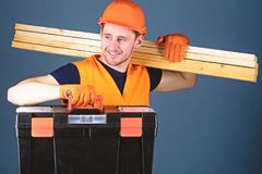 Man in helmet, hard hat holds toolbox and wooden beams, grey background. Professional woodworker concept. Carpenter. Labourer, builder, woodworker on happy stock photography