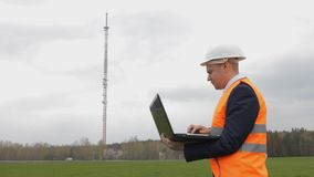 A man in a helmet inspector with a laptop records the data checks and looks toward the telephone tower