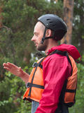 A man in a helmet and lifejacket closeup. On a background of forest Royalty Free Stock Photo