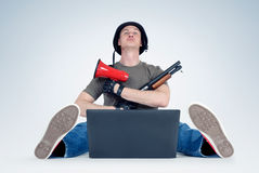 Man in helmet with megaphone and shotgun sitting in front of laptop. Armchair warriors concept Royalty Free Stock Images