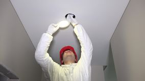 Man with helmet mounting led lighting into ceiling hole stock video footage