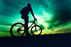 Man with helmet and protective gear on mountain bike against sunset sky Royalty Free Stock Photo