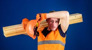 Man in helmet and protective gloves wiping sweat from forehead, blue background. Tired labourer concept. Carpenter. Woodworker, labourer, builder on tired face Royalty Free Stock Photos