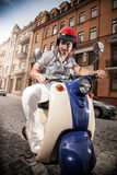 Man in helmet riding scooter Stock Photo