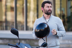 Man with helmet on scooter Stock Images
