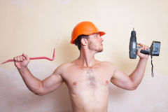 Man in helmet with a screwdriver and crowbar Royalty Free Stock Image