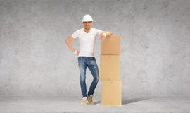 Man in helmet with tower of cardboard boxes Royalty Free Stock Image