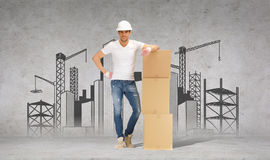 Man in helmet with tower of cardboard boxes Royalty Free Stock Photography