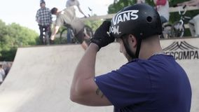 Man in helmet watch at skater in skate park. Summer day. stock video footage