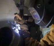 Man in helmet welding. Man in protective helmet welding metal pipes Royalty Free Stock Images