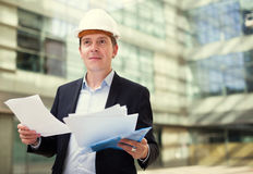 Man in helmet working with documents Stock Photo