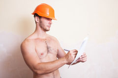 Man in a helmet writes on paper Royalty Free Stock Image