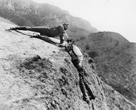 Man helping another man from falling down a cliff. (All persons depicted are no longer living and no estate exists. Supplier grants that there will be no model Royalty Free Stock Photography