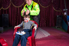 Man Helping Boy Dress Up as Clown on Stage Stock Photo