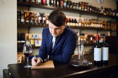 Man helping customers choose the correct wine for a meal or budget. Barmen helping customers choose the correct wine for a meal or budget.close up photo royalty free stock photo