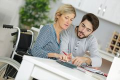 Man helping disabled aunt Royalty Free Stock Image