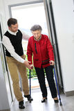 Man helping an elderly lady entering the house. Man helping elderly women with crutches Stock Images