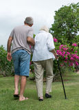 Man helping elderly lady. With walking stick Royalty Free Stock Photography