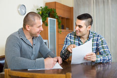 Man helping friend to fill document indoor. Adult men explains to his friend to fill banking document at home Royalty Free Stock Photo