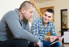 Man helping friend to fill document indoor Stock Photography