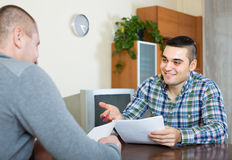 Man helping friend to fill document indoor Royalty Free Stock Images