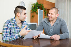 Man helping friend to fill document indoor Royalty Free Stock Photography