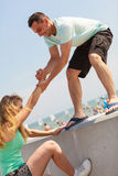 Man helping girlfriend to get on fenece Stock Photography