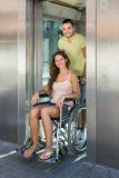 Man helping handicapped girl at elevator Royalty Free Stock Images