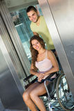 Man helping handicapped girl at elevator Royalty Free Stock Photos