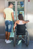 Man helping handicapped girl at elevator Royalty Free Stock Image