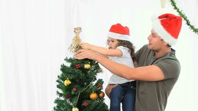 Man helping his daughter to decorate the Christmas tree stock footage