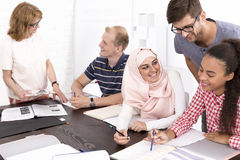 Man helping his freinds to make the language tasks Stock Images
