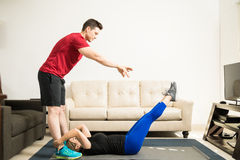 Man helping his girlfriend exercise at home. Profile view of a handsome young men helping his girlfriend with her workout at home royalty free stock photography