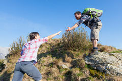 Man Helping His Girlfriend Hiking Royalty Free Stock Image