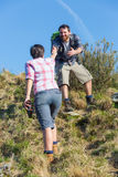 Man Helping His Girlfriend Hiking Stock Photography