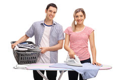 Man helping his girlfriend with ironing Stock Images