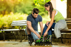 Man helping his girlfriends to put rollerblades Royalty Free Stock Photos