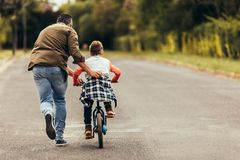 Free Man Helping His Kid In Learning To Ride A Bicycle Stock Photography - 142927652