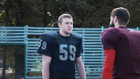 Man helping his mate to put on football jersey. Slow motion of American football player helping his mate to put on jersey before game on field stock footage