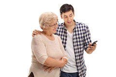 Man helping his mother with cell phone. Young men showing something to an elderly women on his cell phone isolated on white background Royalty Free Stock Photo