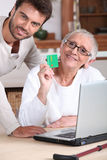 Man helping his mother. Keep a digital record of her healthcare expenses stock images