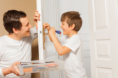 Man helping his son to draw up bolt of door handle. Happy young men holding tool box and helping his kid son to draw up a bolt of door handle at home Royalty Free Stock Photos