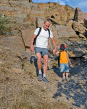 Man helping his son to hike on a rough area Royalty Free Stock Image